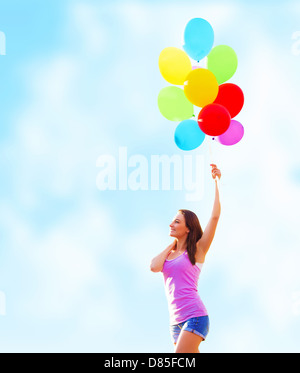 Beautiful young woman holding in hand many colorful balloons on blue sky background, summer time holiday, fun concept - Stock Photo