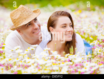 Closeup portrait of beautiful couple lying down on chamomile meadow and looking in one side, summer weekend, happiness - Stock Photo