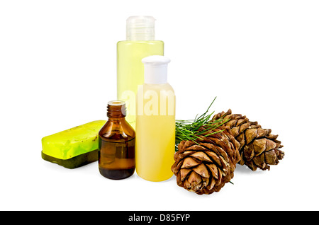 Cedar oil in a bottle, two cedar cones, two green homemade soap, body lotion, shower gel isolated on white background - Stock Photo