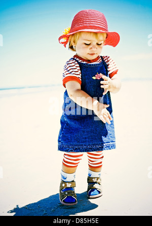 Little baby girl toddler swishing sand off hands on beach - Stock Photo
