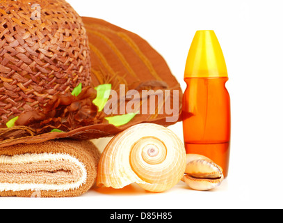 Beach items isolated on white background, straw hat, sunscreen oil, towel and seashell, still life, feminine accessories - Stock Photo