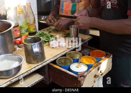 India, Uttar Pradesh, New Delhi, back street scene near New Delhi Railway Station of men preparing vegetables - Stock Photo