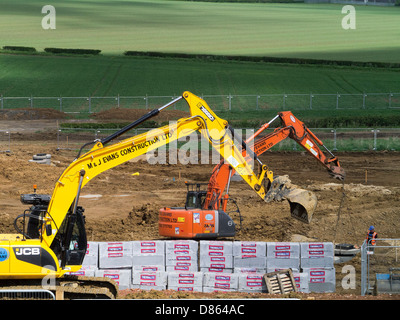 Heavy earth moving machinery preparing rural land for housing development, Grantham, Lincs - Stock Photo
