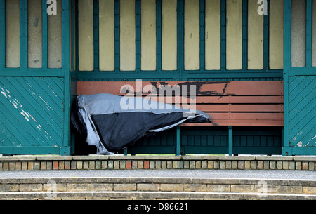 Hove Sussex UK 19 May 2013 - Man sleeping rough in a shelter on Hove seafront - Stock Photo