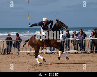 Polo player playing a shot, Veuve Clicquot Polo on the Beach, Watergate Bay, Cornwall, UK 2013 - Stock Photo
