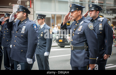 Members of the NYPD and FDNY stand at attention and salute during the playing of the national anthem - Stock Photo