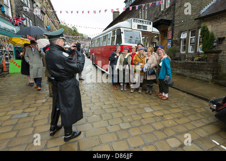 A man in German Army uniform photographing a group of women dressed as land girls in front of a bus. Haworth 1940s - Stock Photo