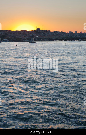 Turkey, Istanbul, View mosque with Golden Horn in foreground at sunset - Stock Photo