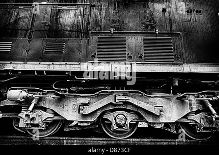 This is a black and white closeup image of train locomotive engine wheels. - Stock Photo