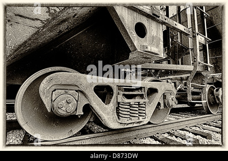 This is a sepia closeup image of train locomotive engine wheels. - Stock Photo