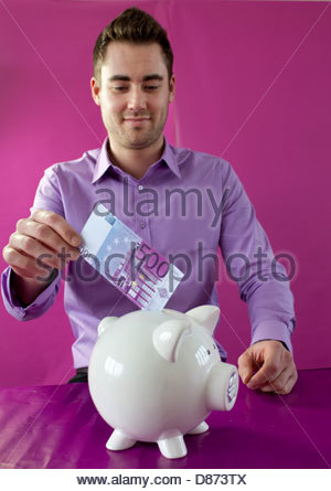 Young man inserting 500 Euro note in a piggy bank - Stock Photo