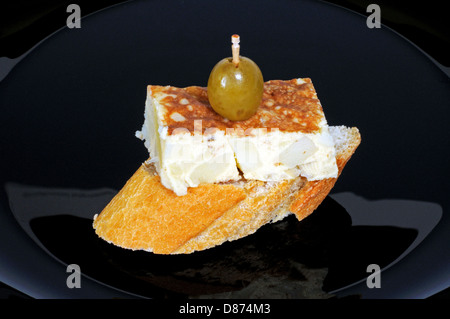 Spanish tortilla tapa topped with a green olive and served on crusty bread, Andalusia, Spain, Western Europe. - Stock Photo