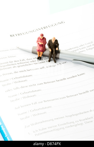 Figurines Sitting On Pen With Advance Directive Form Close Up