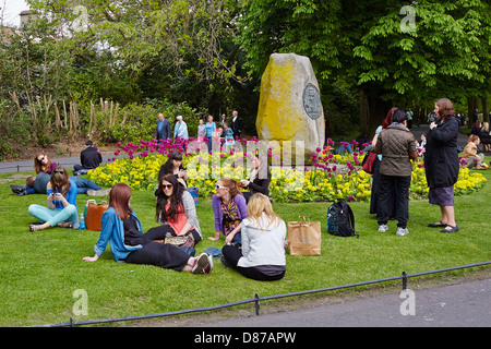 Young people sit and relax on a sunny day in St Stephens Green Park, Dublin, Republic of Ireland - Stock Photo