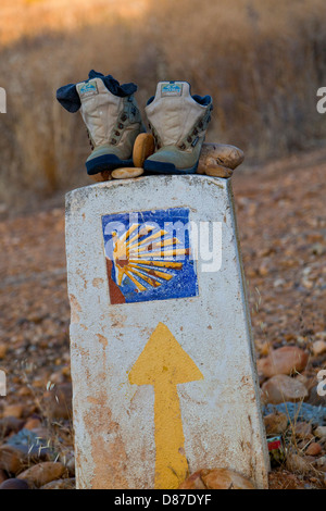 Camino to Santiago; Route Marker, scallop shell and yellow arrow on cement block, rocks and old boots left behind. - Stock Photo