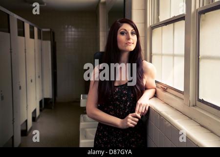 Woman standing next to window in public bathroom - Stock Photo