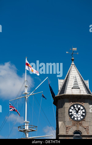 Guernsey flag on flag pole mast and modern seafront buildings ST PETERS PORT GUERNSEY - Stock Photo