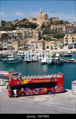 A tour bus waits for ferry passengers on the Maltese island of Gozo. The harbour town of Mgarr is in the background - Stock Photo