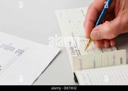 Elderly woman female pensioner writing a Lloyds TSB cheque to pay a large credit card bill. England, UK, Britain - Stock Photo