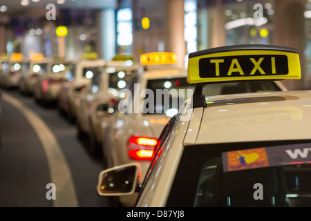Taxis wait at night outside Dusseldorf Airport - Stock Photo