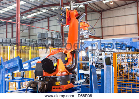 Robotic machinery lifting steel fencing on production line in manufacturing plant - Stock Photo