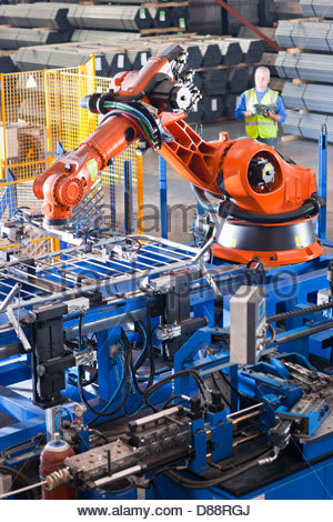 Worker controlling robotic machinery lifting steel fencing on production line in manufacturing plant - Stock Photo