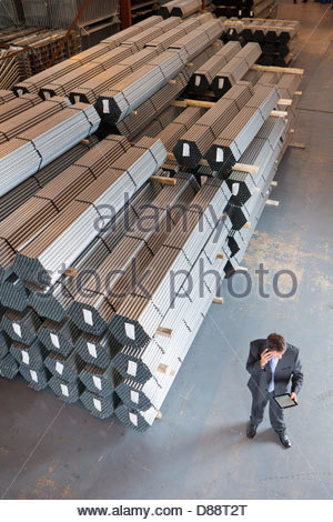 Businessman using cell phone and digital tablet near steel tubing in warehouse - Stock Photo
