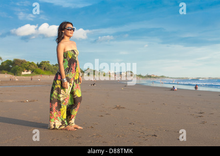 Young asian woman in floral dress on beach in Bali - Stock Photo