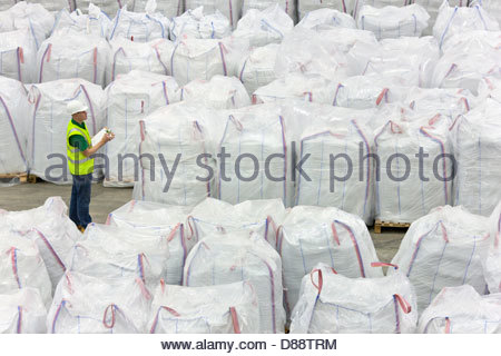 Worker with clipboard among large bags of plastic pellets in warehouse - Stock Photo