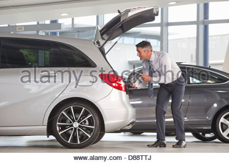Man with brochure looking into hatchback of car in car dealership showroom - Stock Photo