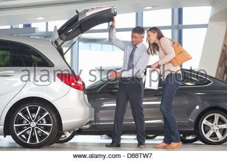 Salesman showing customer hatchback of car in car dealership showroom - Stock Photo