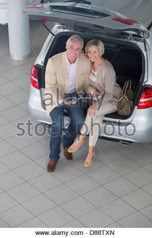 Portrait of smiling couple looking at brochure in hatchback of car in car dealership showroom - Stock Photo