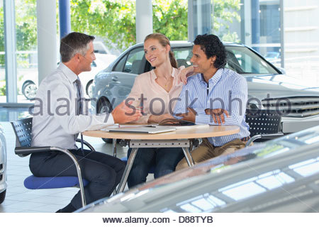 Salesman talking to couple at table in car dealership showroom - Stock Photo