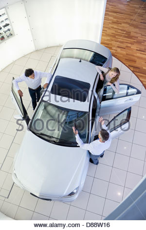 Salesman and couple looking inside car in car dealership showroom - Stock Photo