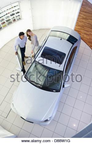 Couple looking inside car in car dealership showroom - Stock Photo