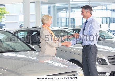 Salesman and customer shaking hands in car dealership showroom - Stock Photo
