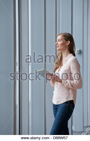 Woman with digital tablet looking out window - Stock Photo