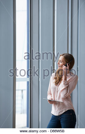 Businesswoman with headset talking on telephone and using digital tablet near window - Stock Photo