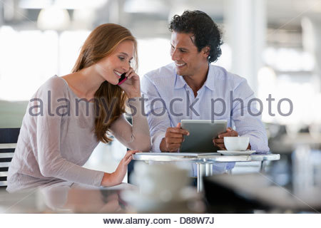 Couple using cell phone and digital tablet at cafe table - Stock Photo