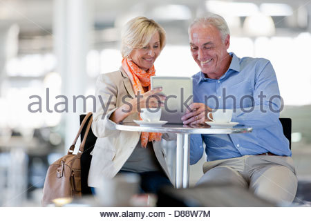 Smiling couple using digital tablet at cafe table - Stock Photo