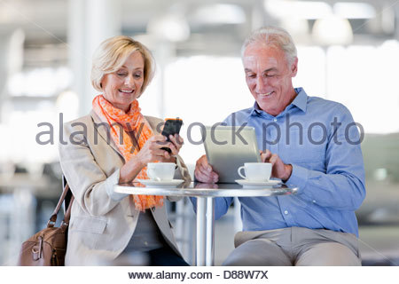 Smiling couple using cell phone and digital tablet at cafe table - Stock Photo
