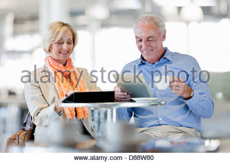 Smiling couple using digital tablets at cafe table - Stock Photo