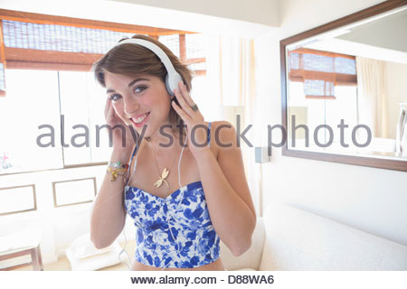 Portrait of smiling young woman wearing headphones - Stock Photo