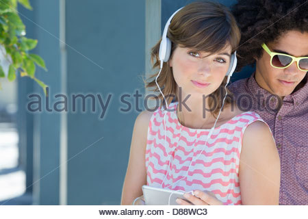 Portrait of young couple wearing headphones with digital tablet - Stock Photo