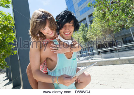Smiling young couple piggybacking and using digital tablet in city - Stock Photo