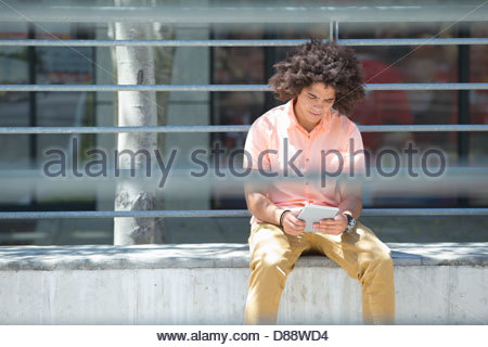Young man using digital tablet in city - Stock Photo