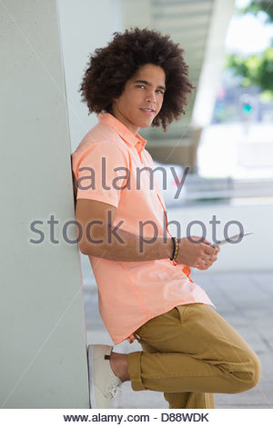 Portrait of smiling young man using digital tablet and leaning against wall - Stock Photo