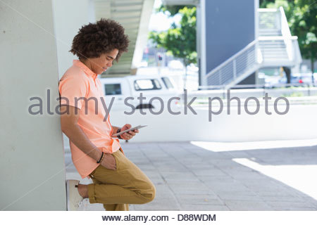 Young man using digital tablet and leaning against wall - Stock Photo