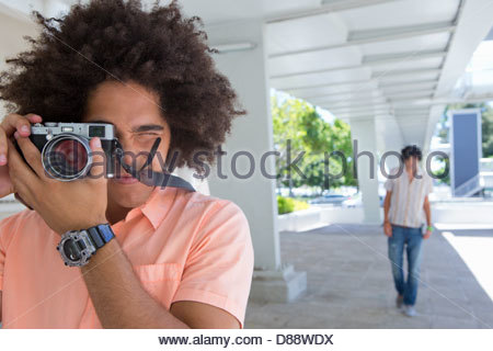 Portrait of young man using camera - Stock Photo