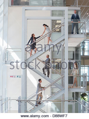 Business people ascending stairs in office - Stock Photo